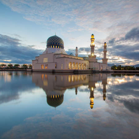 likas: Floating mosque reflection at sunrise with clouds