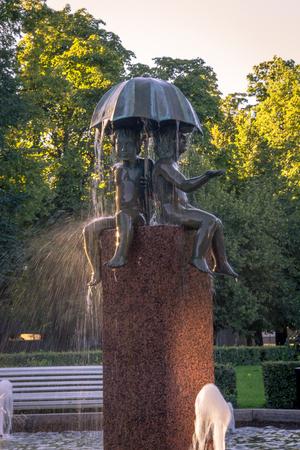 tallin: Scenic summer Beautiful fountain two boys under an umbrella near the Old Town in Tallinn, Estonia Editorial