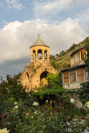 Old dilapidated church on a mountainside in a wild rose garden