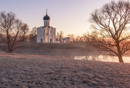 nerl: A misty lake with a boat in front of the church in the early spring at dawn
