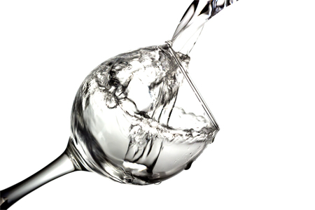 Colorless liquid, water,vodka is poured into a glass, liquid in a speaker, isolated on a white background Stock Photo