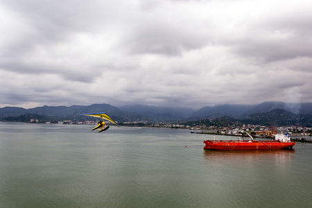 unloading: ocean cargo ship sheltered from a storm in the bay of the port, Batumi, Georgia Stock Photo
