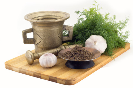 Still Life Spices, cumin ,marigold staminas in a copper vase on a wooden board on a background of a stern stupa for grinding spices, bunches of dill and garlic