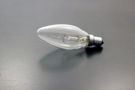 Light bulb turned off over black background