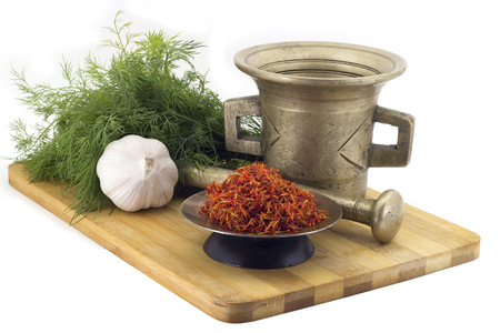 Still Life Spices, Immortin saffron ,marigold staminas in a copper vase on a wooden board on a background of a stern stupa for grinding spices, bunches of dill and garlic