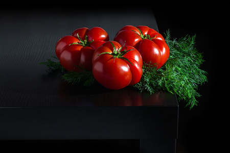 Three large fresh tomatoes and a sprig of dill on a dark wooden background