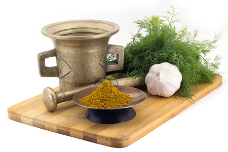 Still Life Spices,Kari spice mix ,marigold staminas in a copper vase on a wooden board on a background of a stern stupa for grinding spices, bunches of dill and garlic
