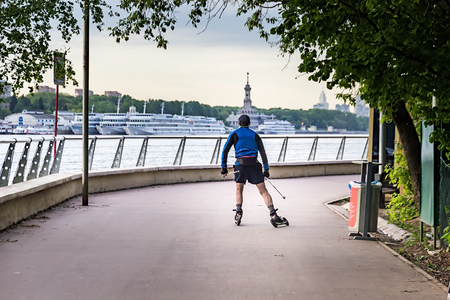 Early in the morning in the park the ski roller skates along the picturesque embankment opposite the river port