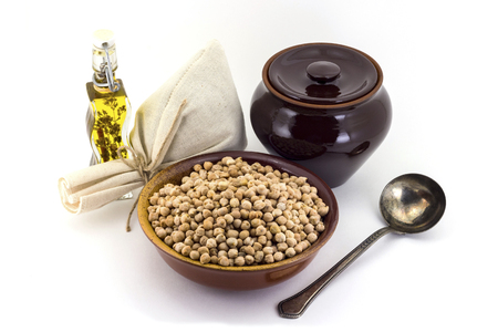 Still life of chick peas in ceramic pial, ceramic pot, old spoon and canvas bag for cereals, oil with spices and seasonings, isolated on white background