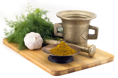 karri: Still Life Spices,Kari spice mix ,marigold staminas in a copper vase on a wooden board on a background of a stern stupa for grinding spices, bunches of dill and garlic