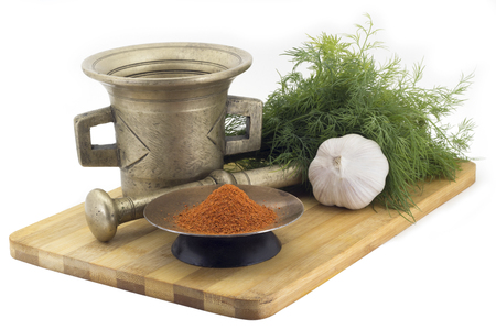 bunches: Still Life Spices,mix hot peppers ,marigold staminas in a copper vase on a wooden board on a background of a stern stupa for grinding spices, bunches of dill and garlic