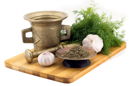 bunches: Still Life Spices, celery ,marigold staminas in a copper vase on a wooden board on a background of a stern stupa for grinding spices, bunches of dill and garlic
