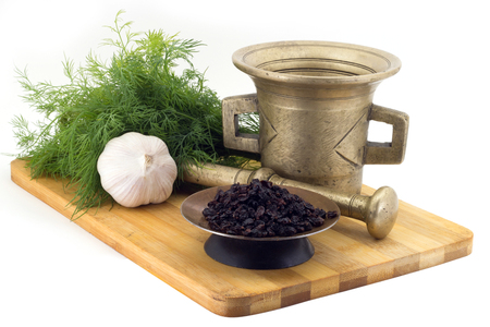 Still Life Spices,fragrant sumac ,marigold staminas in a copper vase on a wooden board on a background of a stern stupa for grinding spices, bunches of dill and garlic