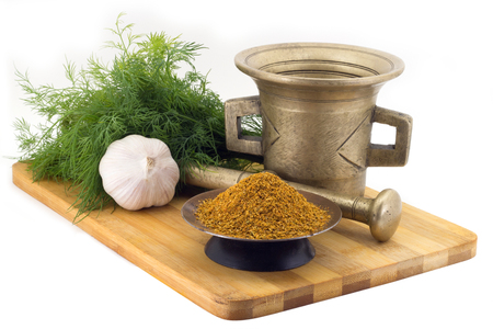 bunches: Still Life Spices, seasonning for pilaf,marigold staminas in a copper vase on a wooden board on a background of a stern stupa for grinding spices, bunches of dill and garlic