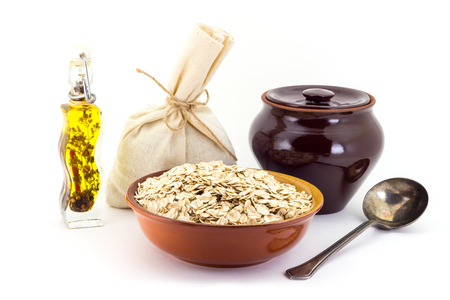 Still life of Oatsmeal cereal in ceramic pial, ceramic pot, old spoon and canvas bag for cereals, oil with spices and seasonings, isolated on white background