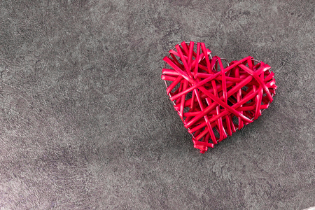 Redheart-shaped straw weave on a gray textured background Stok Fotoğraf