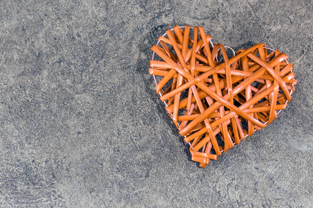 Orange heart-shaped straw weave on a gray textured background Stok Fotoğraf