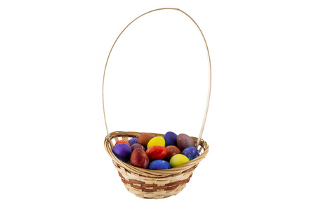 Easter eggs in wicker basket isolated on white background