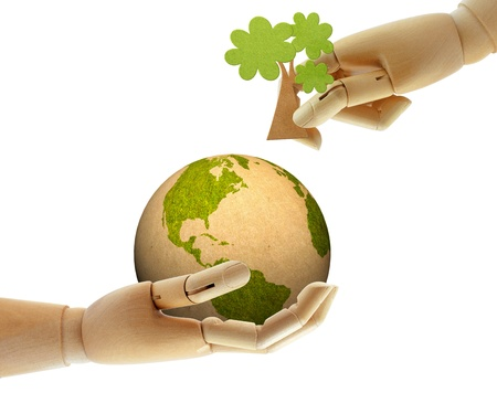 wooden hand help growing tree on earth together Stock Photo