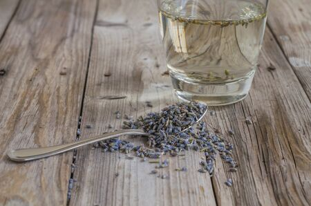 a tea spoon of dried lavender on wood table for herbal tea