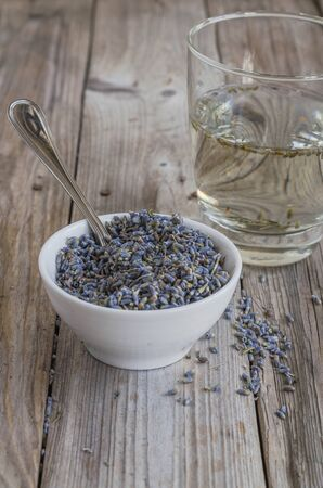 a white cup of dried lavender with stainless tea spoon on wood table Stock Photo