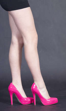 Close Up of Womans Legs Wearing Pink High Heels and Mini Skirt photo