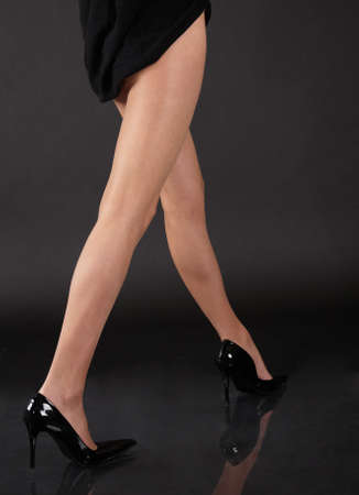 Womans Legs in Sheer Pantyhose and Black Skirt and High Heel Shoes photo