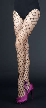 fishnets: Legs in Fishnet Pantyhose and Purple High Heels