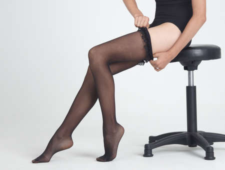 ankles sexy: Woman Putting on Black Stockings Stock Photo