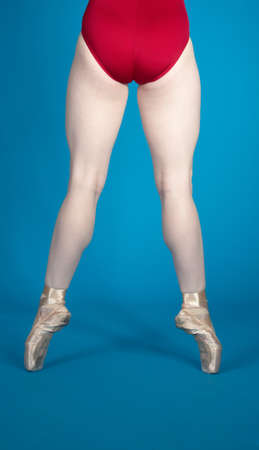 pointed: Back of Ballerina s Legs En Pointe Wearing a Red Leotard Isolated Against a Blue Studio Background Stock Photo