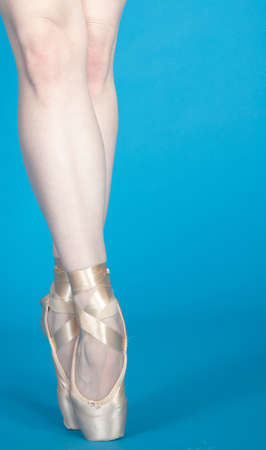 Ballerina s Legs En Pointe Isolated Against a Blue Studio Background photo
