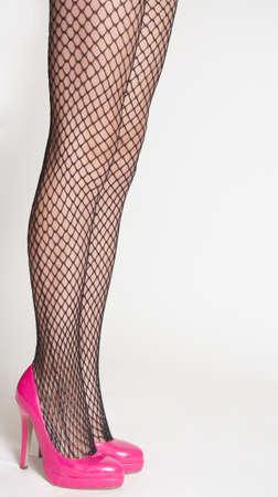 Woman s Legs Wearing Black Fishnet Pantyhose and Pink High Heels photo