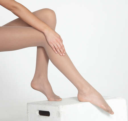 calves: Woman s Legs Wearing Sheer Nude Pantyhose Isolated Against a White Studio Background
