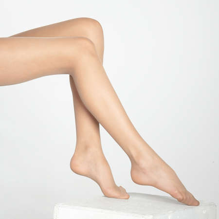 Woman s Legs Wearing Sheer Nude Pantyhose Isolated Against a White Studio Background photo