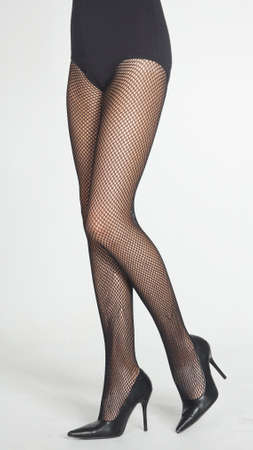 Woman s Legs Wearing Black Fishnet Pantyhose and Black High Heels photo
