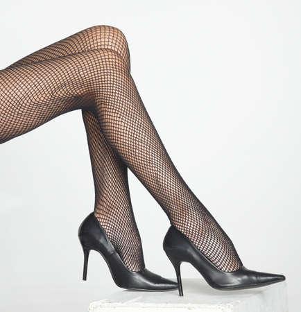 팬티 스타킹: 블랙 피쉬 넷 팬티 스타킹과 블랙 하이 힐을 착용하는 여성의 다리 스톡 사진