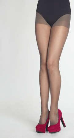 piernas con tacones: Piernas de mujer s usando medias de Sheer, Leotardo Negro y p�rpura tacones altos aislados contra un fondo blanco del estudio