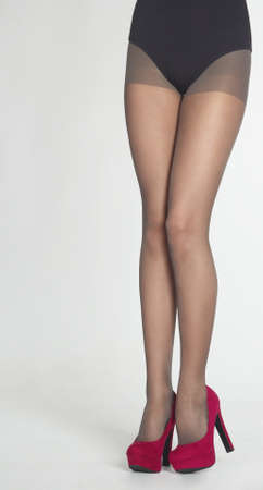 stockings feet: Woman s Legs Wearing Sheer Pantyhose, Black Leotard, and Purple High Heels  Isolated Against a White Studio Background