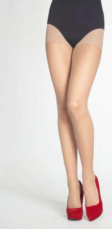 pantimedias: Piernas de mujer s usando medias de Sheer, Leotardo Negro y p�rpura tacones altos aislados contra un fondo blanco del estudio