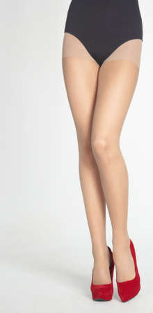 ankles sexy: Woman s Legs Wearing Sheer Pantyhose, Black Leotard, and Purple High Heels  Isolated Against a White Studio Background