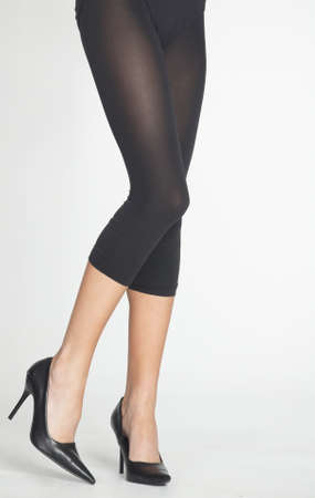stockings heels: Woman s  Legs Wearing Black Capri Tights, Black Heels and Boy Shorts Isolated Against a White Studio Background