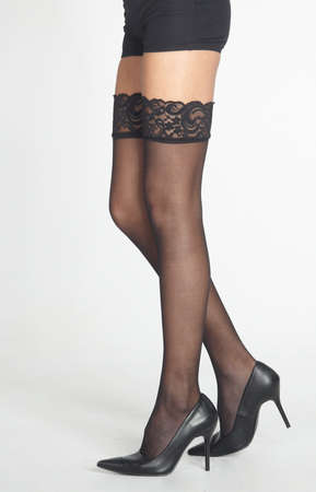 Woman s Legs Wearing Black Lace Stockings, Heels, and Boy Shorts Isolated Against a White Studio Background