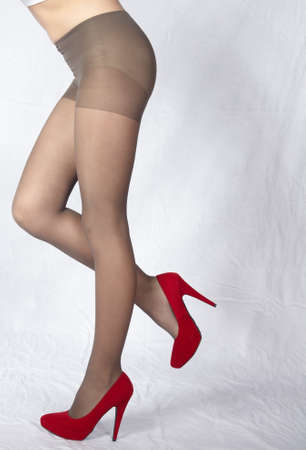 Woman s Legs Wearing Sheer Pantyhose and Red High Heels photo