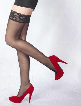 medias mujer: Mujer s Piernas Usar medias negras de encaje y zapatos de tac�n rojo Foto de archivo
