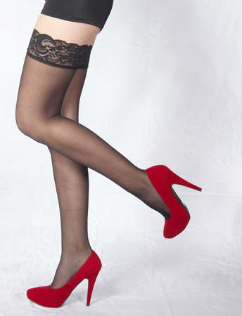 Woman s Legs Wearing Black Lace Stockings and Red High Heels photo