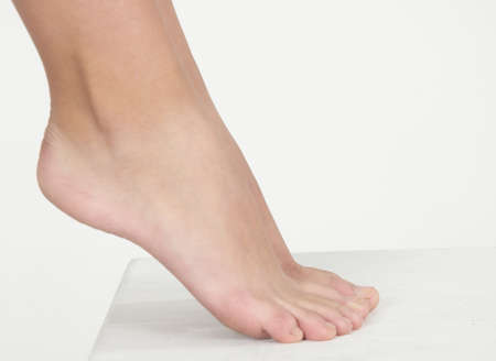Woman s Bare Feet Against a White Studio Background