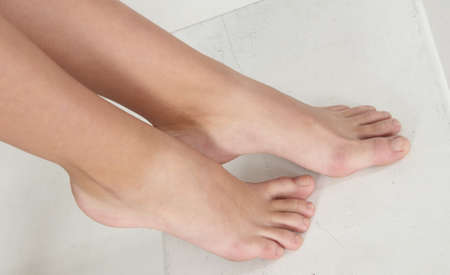 human toe: Overhead View of Woman s Bare Feet Against a White Studio Background Stock Photo