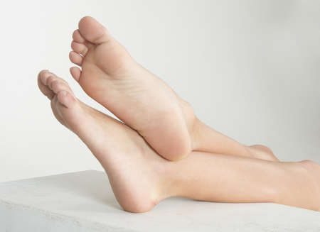 feet crossed: Woman s Bare Feet with her Ankles Crossed and Elevated