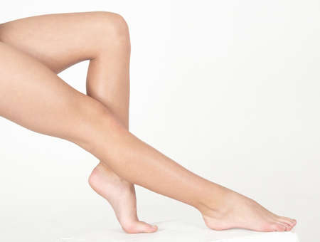ankles sexy: Woman s Bare Legs Against a White Studio Background Stock Photo