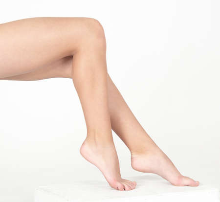 Woman s Bare Legs Against a White Studio Background photo